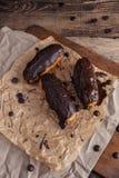 Eclairs o Profiterole con cioccolato fondente Cucinando sul cuocere SH Fotografia Stock