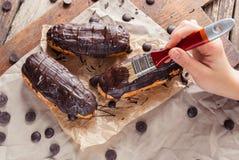 Eclairs o Profiterole con cioccolato fondente Cucinando sul cuocere SH Fotografie Stock Libere da Diritti