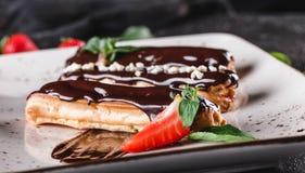 Eclairs o profiteroles hechos en casa de la torta con natillas, chocolate y fresas en el fondo oscuro servido con la taza de caf? foto de archivo libre de regalías