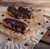 Eclairs ou Profiterole com chocolate escuro Cozimento no cozimento Sh imagens de stock royalty free