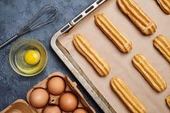 Eclairs ou profiterole que preparam-se com os ovos no fundo da folha de cozimento fotos de stock