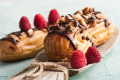 Eclairs with peanuts, chocolate icing and raspberries Royalty Free Stock Photography