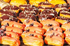 Eclairs with pink glaze close-up. With dark chocolate sun day stock images
