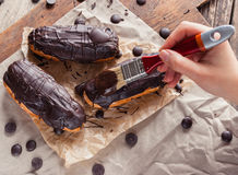 Eclairs or Profiterole with Dark Chocolate. Cooking on Baking Sh Stock Photography