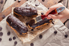 Eclairs or Profiterole with Dark Chocolate. Cooking on Baking Sh Royalty Free Stock Images