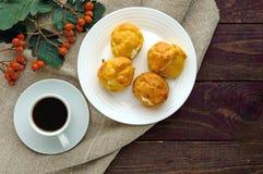 Eclairs recientemente cocidos de los bollos rellenos con requesón picante y una taza de café y de x28; espresso& x29; en un fondo imágenes de archivo libres de regalías