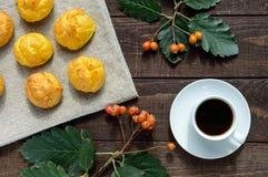 Eclairs recientemente cocidos de los bollos y una taza de café y de x28; espresso& x29; en un fondo de madera oscuro Desayuno lig imágenes de archivo libres de regalías