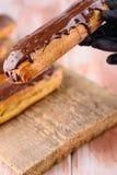 Eclairs saborosos e bonitos com chocolate em uma placa de madeira Sobremesa apetitosa Fontes do partido imagem de stock royalty free