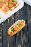 Eclairs saborosos e bonitos em uma placa de madeira Sobremesa apetitosa com peixes, o pepino, queijo e verdes vermelhos imagem de stock