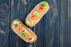 Eclairs saborosos e bonitos em uma placa de madeira Sobremesa apetitosa com peixes, o pepino, queijo e verdes vermelhos foto de stock royalty free