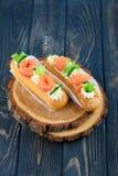 Eclairs saborosos e bonitos em uma placa de madeira Sobremesa apetitosa com peixes, o pepino, queijo e verdes vermelhos imagens de stock
