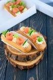 Eclairs saborosos e bonitos em uma placa de madeira Sobremesa apetitosa com peixes, o pepino, queijo e verdes vermelhos fotografia de stock