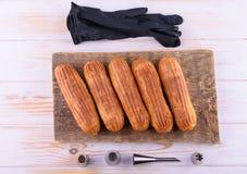 Eclairs saborosos e bonitos em uma placa de madeira Sobremesa apetitosa Fontes do partido imagens de stock royalty free