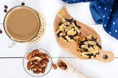Eclairs som täckas med mörk choklad- och mandelflingagarnering, cappuccinokopp Royaltyfri Fotografi