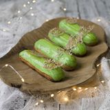 Eclairs with tangerine jelly, orange mousse and mascarpone cream decorated with green icing and gold lace decoration on stock photo