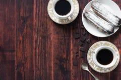 Eclairs, tazze e cioccolato di cioccolato Immagini Stock
