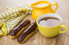 Eclairs, tea in cup, jug of milk, checkered napkin. On wooden table Royalty Free Stock Image