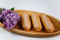 Eclairs on white backgroung. On wooden plate with flowers Royalty Free Stock Photography