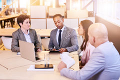 Eclectic group of four business professionals conducting a meeting stock images