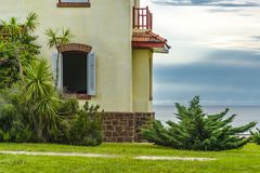 Eclectic Style Chalet Exterior Facade. Exterior view of waterfront eclectic old style chalet at field, Maldonado, Uruguay Stock Photos