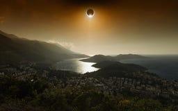 Eclipse solar total en cielo que brilla intensamente rojo oscuro sobre ciudad de playa fotos de archivo libres de regalías