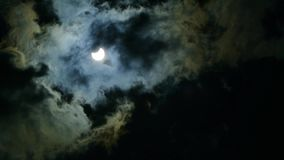 The eclipse of the sun in the sky. The eclipse through the cloud stock video