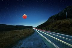 Eclissi eccellente della luna del sangue blu e tracce dell'automobile Fotografia Stock