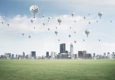 eco与飞行在城市上的浮空器的绿色生活的概念 库存照片