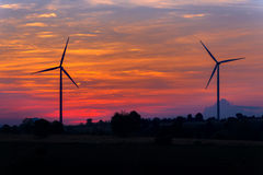 Eco力量在有日落的风轮机农场 免版税库存照片