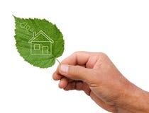 Eco房子概念,拿着eco在自然孤立的手房子象 免版税库存照片