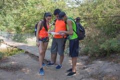 Eco旅游业和健康生活方式概念 有背包的年轻远足者女孩末端男孩 旅客,在度假读地图的远足者 免版税库存图片