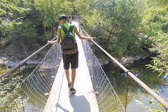 Eco旅游业和健康生活方式概念 有背包的年轻远足者男孩 在吊桥的旅客旅行去迁徙衣服 免版税库存图片