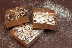 Eco样式礼品包装材料 用木激光裁减雪花装饰的三个礼物盒 顶视图 抽象背景褐色排行照片 免版税库存照片