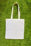 Eco袋子由没有漆的100棉花制成在绿色人为草背景 顶视图 大模型 免版税图库摄影