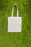 Eco袋子由没有漆的100棉花制成在绿色人为草背景 顶视图 大模型 免版税库存照片