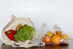 Eco återvinningsbar påse med grönsaker och plastpåsen med frukter royaltyfria bilder