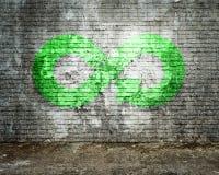 ECO, économie circulaire, symbole vert fluorescent de flèche d'infini, mur de briques photographie stock libre de droits