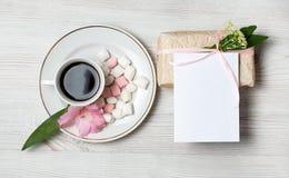 Eco-Artgeschenkbox und Grußkarte mit rosa Blumen und Kaffeetasse a über dem hölzernen Hintergrund Draufsicht, flache Lage Stockbilder