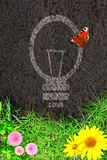 Eco background with green grass and light bulb silhouette Stock Photo
