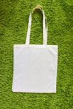Eco bag made of unpainted 100 cotton on a green artificial grass background. Top view. Mockup Royalty Free Stock Photography