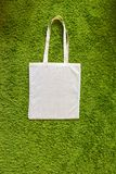 Eco bag made of unpainted 100 cotton on a green artificial grass background. Top view. Mockup Stock Photos