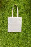 Eco bag made of unpainted 100 cotton on a green artificial grass background. Top view. Mockup Royalty Free Stock Photo