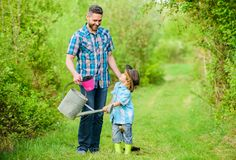 Eco-Bauernhof Benutzen Sie Gie?kanne und Topf Gartenger?te kleiner Jungenkinderhilfsvater bei der Landwirtschaft Vater und Sohn i stockfotos