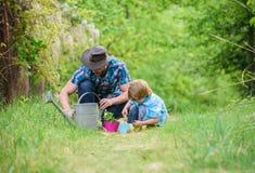 Eco-Bauernhof Gie?kanne, Topf und Hacke Gartenger?te kleiner Jungenkinderhilfsvater bei der Landwirtschaft Vater und Sohn im Cowb lizenzfreie stockbilder