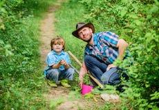 Eco-Bauernhof Hacke, Topf und Schaufel Gartenger?te kleiner Jungenkinderhilfsvater bei der Landwirtschaft Vater und Sohn im Cowbo stockfotografie