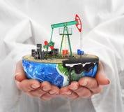 Eco-begrepp En snittplanet med olje- pumpjack i kvinnas handiso Arkivbilder