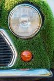 Eco bil som räknas med konstgjort grönt gräs Arkivfoton