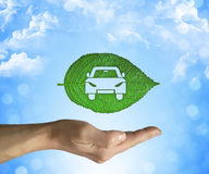 Eco car. Opened hand holding a green leaf with a car icon inside on a blue sky background. Eco car concept Royalty Free Stock Photography