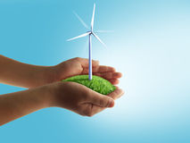 Eco concept. With hands and wind turbines Royalty Free Stock Photo