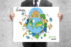 Eco concept. Businessman in suit holding creative sketching of globe with natural healthy lifestyle icons on concrete wall background. Eco concept Stock Photos